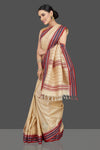 Shop stunning cream tussar silk saree online in USA with blue and red temple border. Look beautiful on weddings and special occasions in stunning Kanchipuram saris, pure silk sarees, handwoven saris from Pure Elegance Indian fashion store in USA.-full view