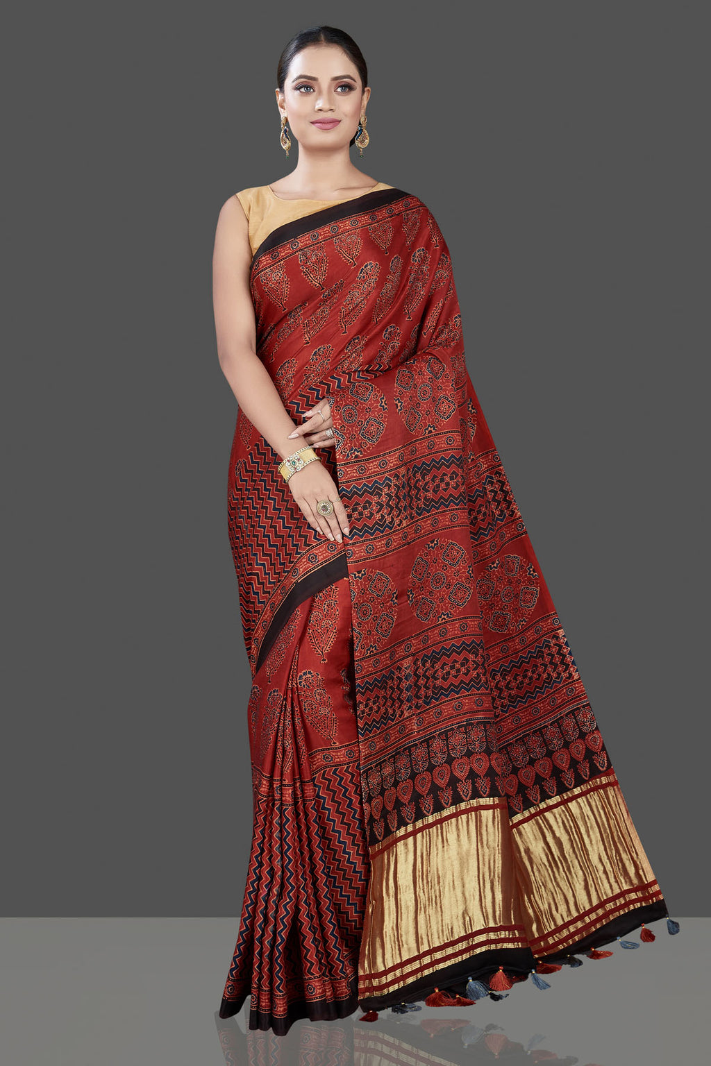 Shop beautiful red Ajrakh print saree online in USA with golden zari pallu. Be the talk of the occasion in exquisite designer sarees, pure silk sarees, tussar saris, embroidered sarees, handloom sarees from Pure Elegance Indian fashion store in USA.-full view