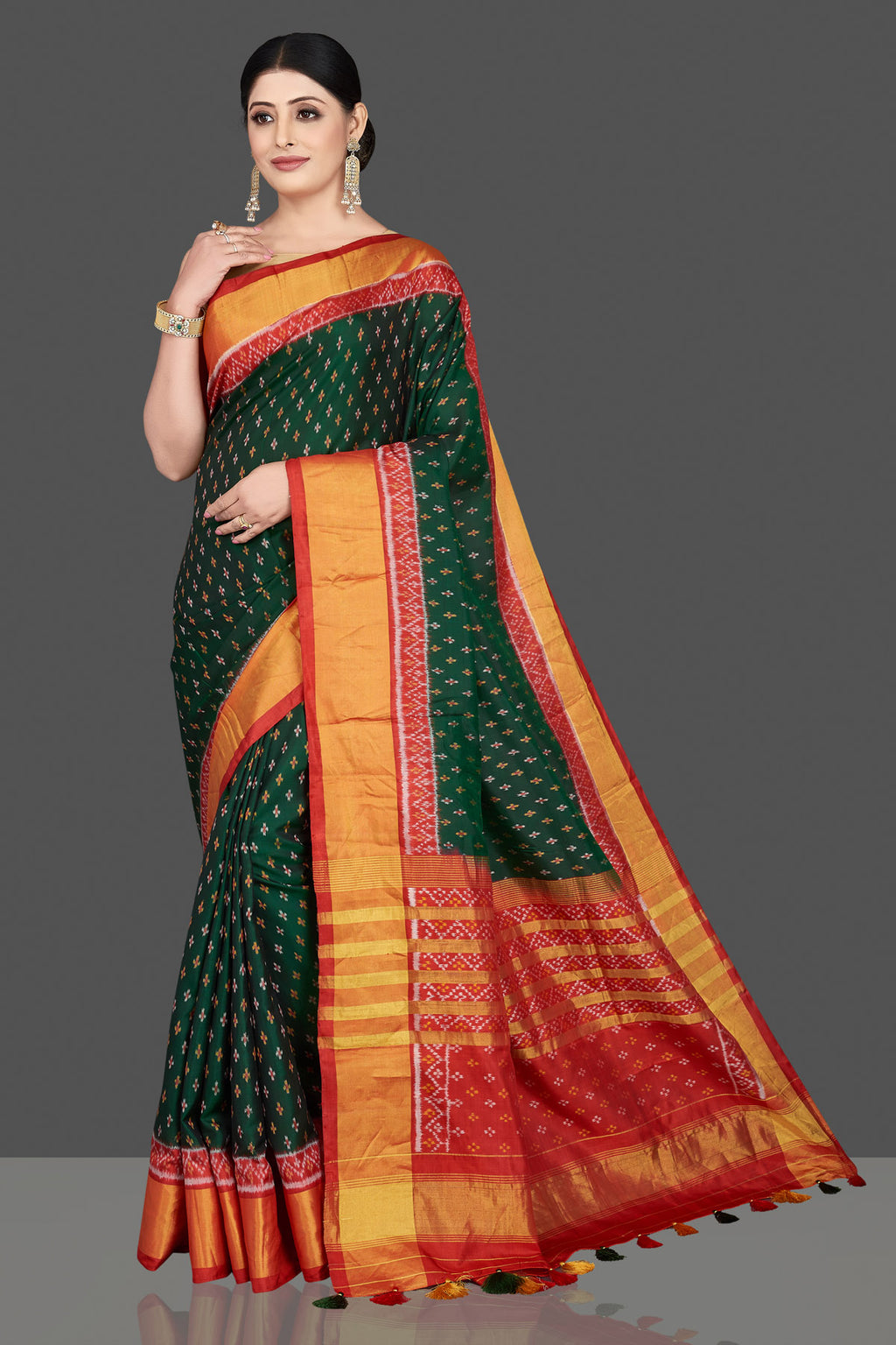 Buy gorgeous dark green patola ikkat sari online in USA with golden zari border. Be the center of attraction at weddings and special occasions in exquisite designer sarees, handwoven silk sarees, embroidered saris, pure silk sarees from Pure Elegance Indian fashion store in USA.-full view