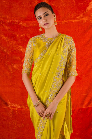 Buy yellow embroidered silk saree online in USA. Saree has fine heavy embroidery work and border. Blouse of yellow color has detailed embroidery work and net sleeves of elbow lenght. Be the talk of parties and weddings with exquisite designer sarees from Pure Elegance Indian clothing store in USA.Shop online now.-close up