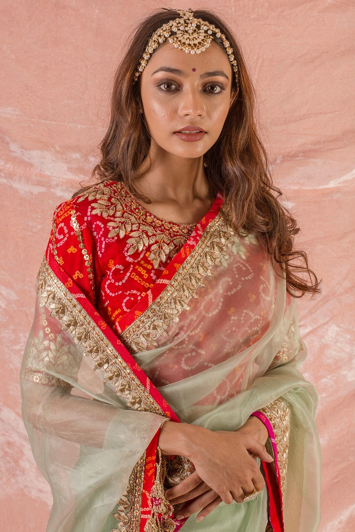Buy beautiful green embroidered handloom saree with matching red blouse online in USA. Saree is crafted with fine embroidery and heavy gold border and matching heavy red bandhej blouse. Be the talk of parties and weddings with exquisite designer sarees from Pure Elegance Indian clothing store in USA.Shop online now.-close up