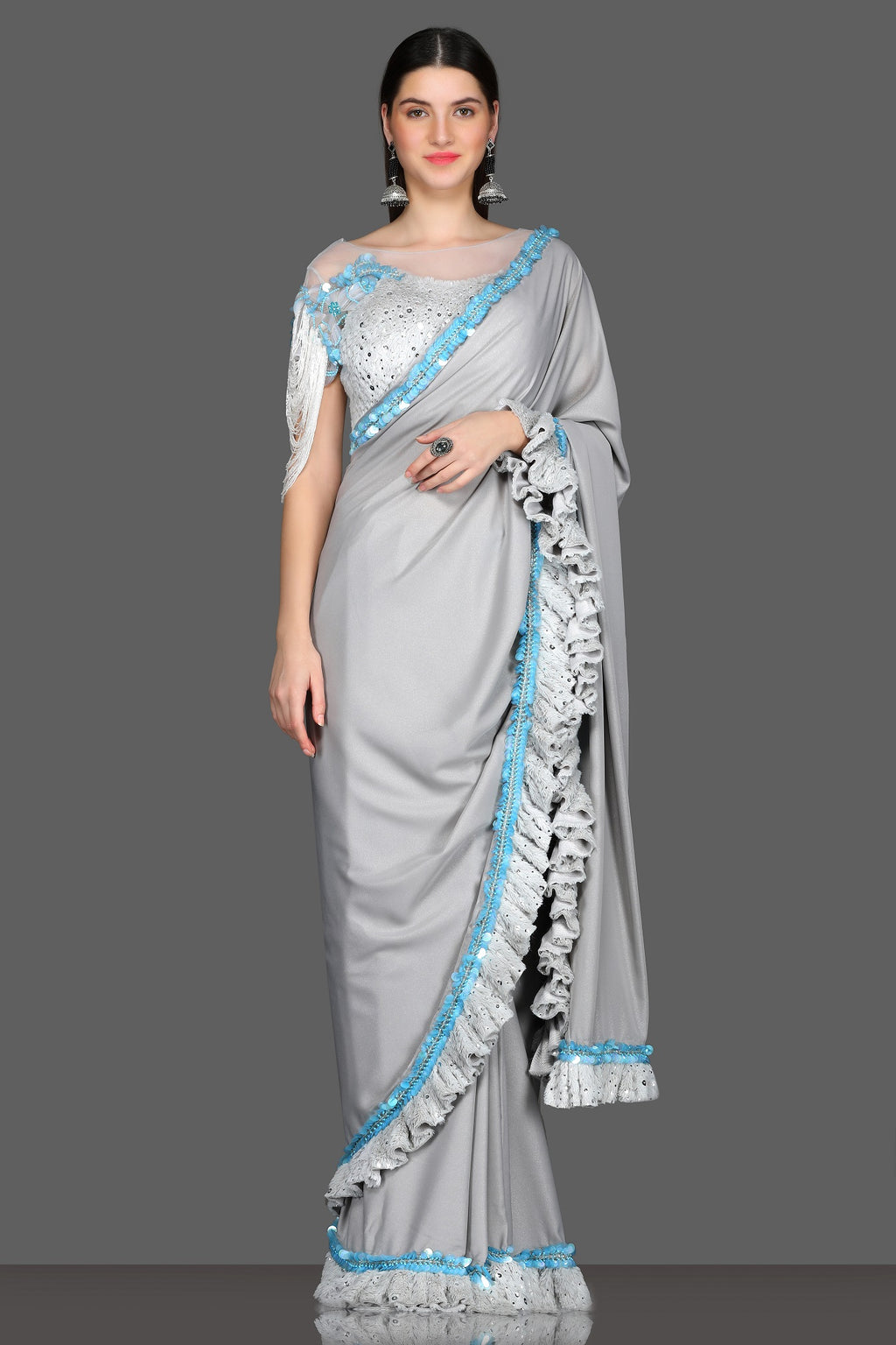 Shop stunning light grey designer ruffle saree online in USA with embroidered sheer saree blouse. Make a fashion statement at weddings with stunning designer sarees, embroidered sarees with blouse, wedding sarees, handloom sarees from Pure Elegance Indian fashion store in USA.-full view