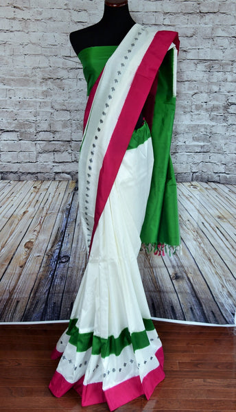 90A772 This white ikkat silk saree from India with vibrant green & pink borders is sure to be a lovely addition in your party wear sarees collection Buy this simple saree online at our ethnic clothing store online in USA. The saree for sale is simple, yet eye-catching!