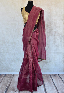 90B022 Maroon linen saree with a golden readymade blouse. This plain saree, available online at Pure Elegance makes for a striking Indian outfit and is well suited for Indian weddings & receptions.