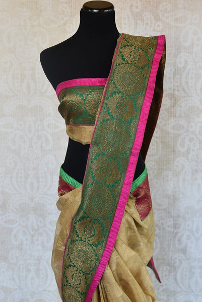 90B813 Sophisticated golden beige saree with a classic green and gold brocade border & a vibrant pink trim. Buy this lovely saree from India at our ethnic clothing store Pure Elegance online in USA.