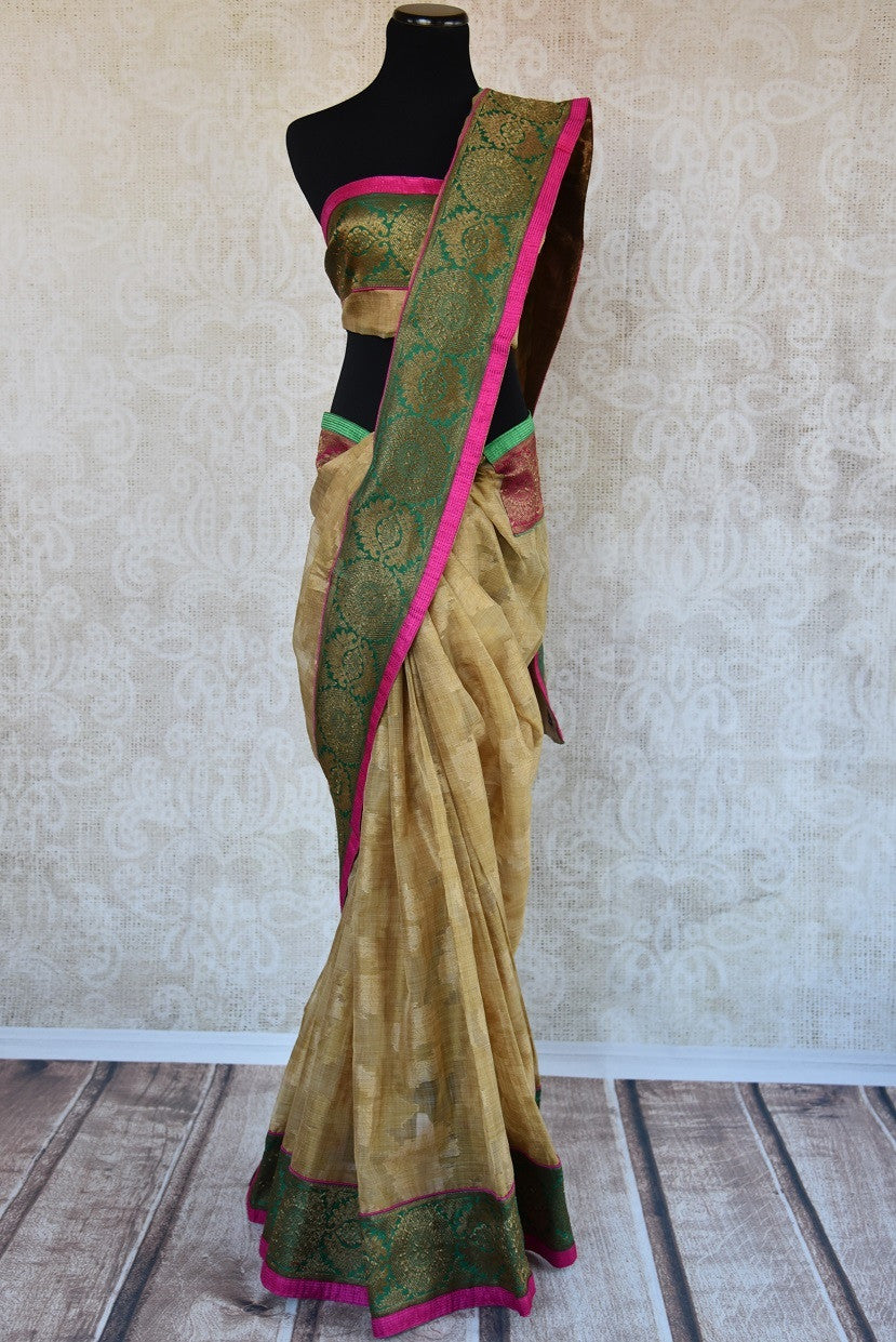 90B813 An elegant gold saree with a green and gold brocade border & a vibrant pink trim. Buy this traditional saree from India at our ethnic wear store Pure Elegance online or in Edison USA.