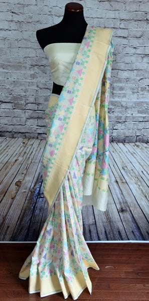 90B250 Beautiful white Banarasi weave silk saree with a cream border and classic pastel colored floral phulkari design. Buy this party wear saree online in USA from our ethnic Indian wear store - Pure Elegance.