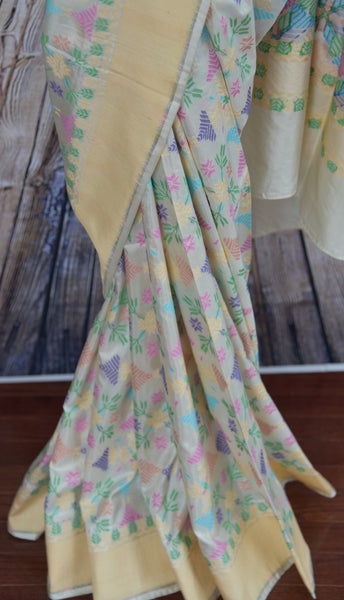 90B250 Beautiful white Banarasi weave silk saree with a cream border and classic pastel colored floral phulkari design. Buy this party wear saree in USA from our ethnic wear store - Pure Elegance, online in USA.