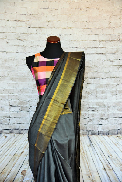90B505 Simple grey bhagalpur tussar saree with a classic golden border. This Indian outfit can be bought online at Pure Elegance and is ideal for Indian wedding receptions & parties. Versatile and striking, you'll love having this saree in your Indian clothing wardrobe.