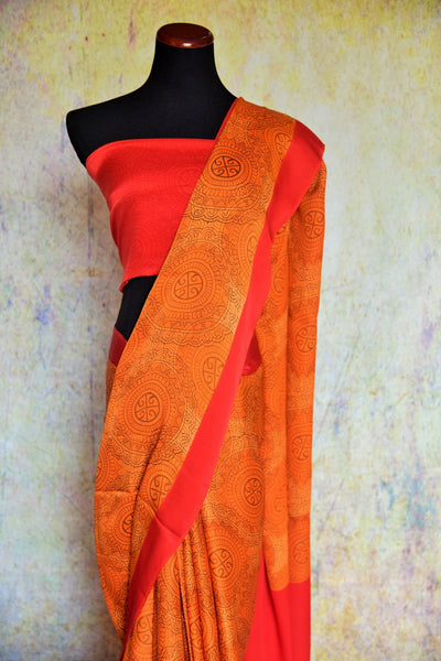 90B568 Keep it strikingly stunning in this orange crepe saree with a red border trim. The ethnic printed saree makes for a wonderful choice for wedding or party wear saree. Buy it online in USA at our Indian wear store - Pure Elegance.