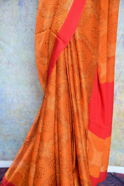 90B568 Keep it gorgeous in this vibrant orange crepe saree with a red border trim. The classic printed ethnic outfit makes for the perfect Indian wedding or party wear saree. Buy it online at our Indian ethnic wear store - Pure Elegance.