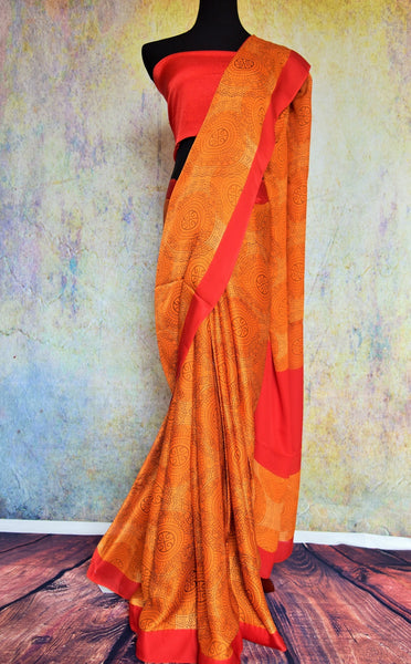90B568 Keep it bold and beautiful in this orange crepe saree with a red border trim. The printed ethnic outfit makes for the perfect Indian wedding or party wear saree. Buy it online at our Indian fashion store - Pure Elegance.