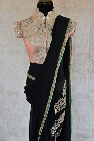 90C147 Bold georgette saree with embroidery work and a thin gold border. Buy this black party wear saree with peach blouse at Pure Elegance - our online ethnic wear store in USA.