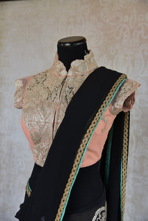 90C147 Georgette saree with embroidery work and a thin gold border. This black party wear saree with peach blouse is available online at our Indian fashion store - Pure Elegance in USA.