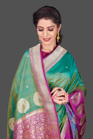 Shop green Banarasi silk sari in USA with magenta zari border. Shop beautiful Banarasi silk sarees, tussar saris, pure muga silk saris in USA from Pure Elegance Indian fashion boutique in USA. Get spoiled for choices with a splendid variety of Indian sarees to choose from! Shop now.-closeup