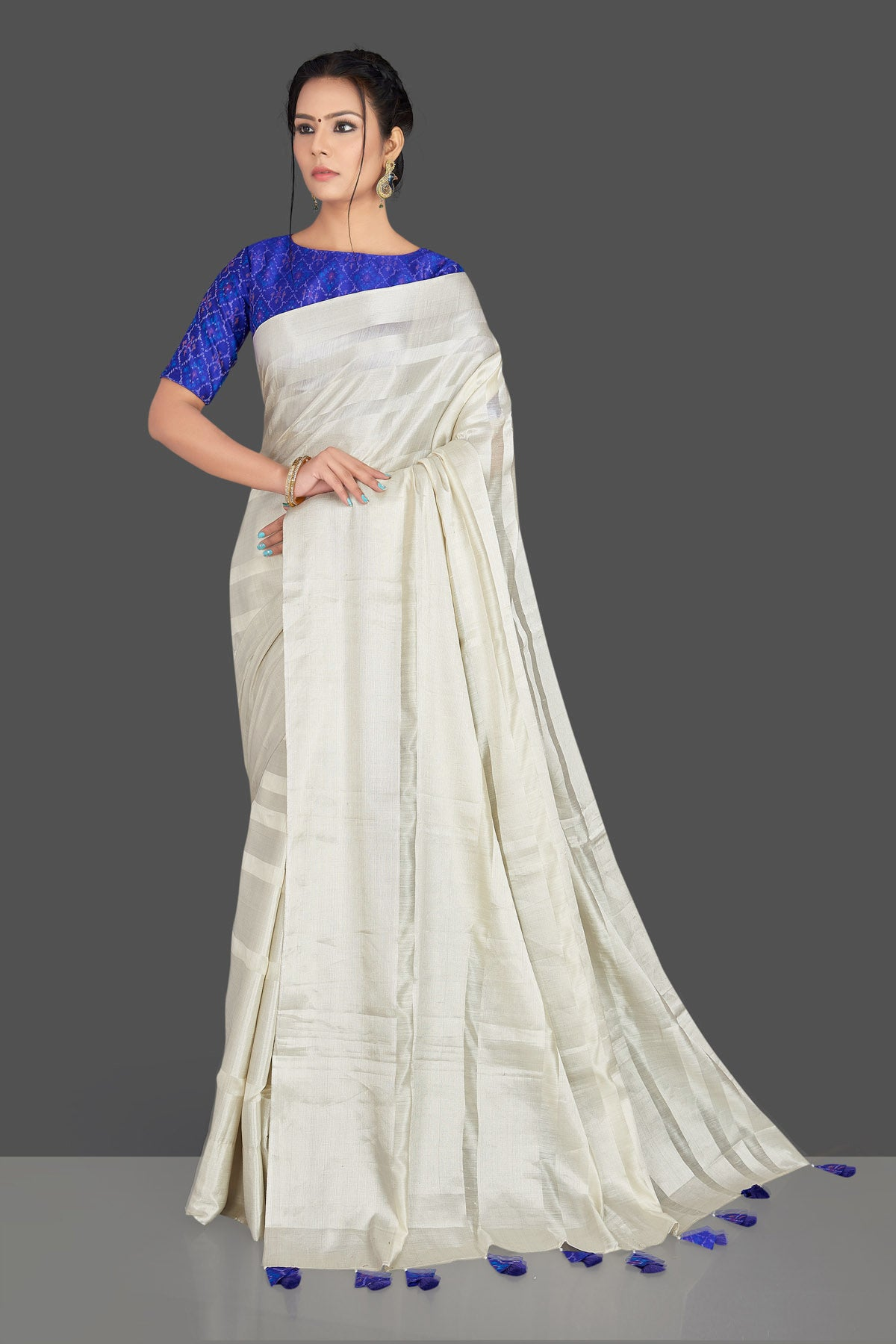 Buy lovely off-white tassar silk sari online in USA with blue patola ikkat saree blouse. Make your ethnic wardrobe rich with timeless handwoven sarees, tissue sarees, silk sarees, tussar saris from Pure Elegance Indian clothing store in USA. Find all the designer sarees for special occasions under one roof!-full view