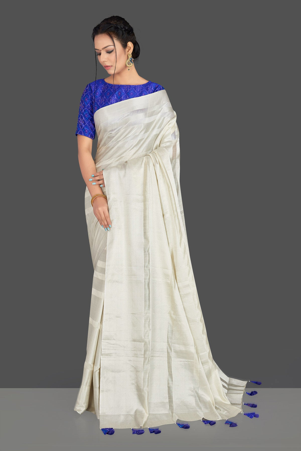 Buy lovely off-white tassar silk sari online in USA with blue patola ikkat saree blouse. Make your ethnic wardrobe rich with timeless handwoven sarees, tissue sarees, silk sarees, tussar saris from Pure Elegance Indian clothing store in USA. Find all the designer sarees for special occasions under one roof!-front