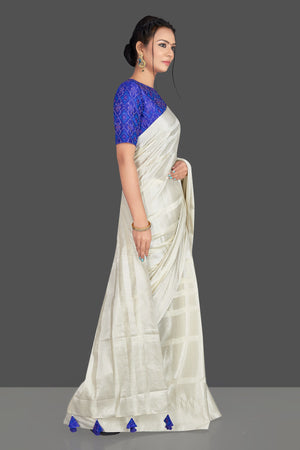 Buy lovely off-white tassar silk sari online in USA with blue patola ikkat saree blouse. Make your ethnic wardrobe rich with timeless handwoven sarees, tissue sarees, silk sarees, tussar saris from Pure Elegance Indian clothing store in USA. Find all the designer sarees for special occasions under one roof!-side