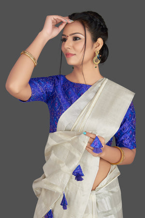 Buy lovely off-white tassar silk sari online in USA with blue patola ikkat saree blouse. Make your ethnic wardrobe rich with timeless handwoven sarees, tissue sarees, silk sarees, tussar saris from Pure Elegance Indian clothing store in USA. Find all the designer sarees for special occasions under one roof!-closeup