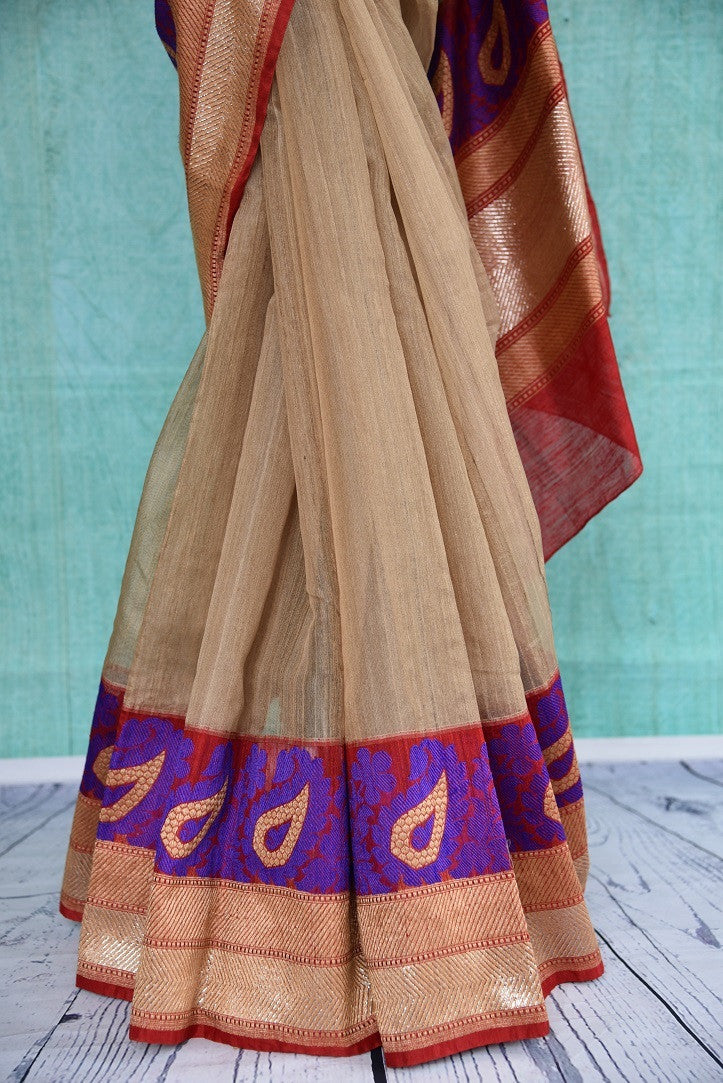 90B948 Traditional matka resham Banarasi saree at our Indian clothing store in USA. The cream saree with multicolor border and pallu and a red blouse is an ethnic outfit that's must have in your Indian clothing collection.