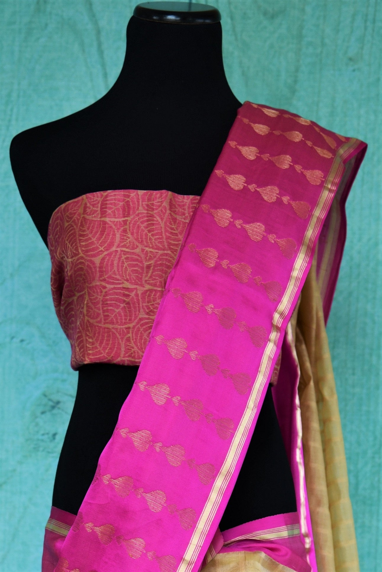 90B280 Shop this beige and pink muga Banarasi saree online at Pure Elegance. Topped with a vibrant pink border with golden pattern, it makes for the perfect festive wear Indian outfit.
