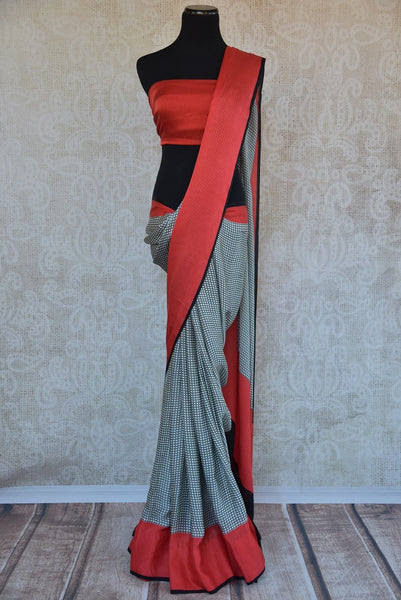 90B570 This printed crepe silk saree is ideal for party wear & small Indian wedding functions. With a checked pattern & red border, this Indian outfit is simple, contemporary and gorgeous!