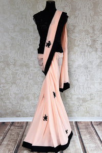 90D250 This black and peach georgette saree with an embroidered designer blouse and black butis and border is sure to make a striking impression. Buy this party wear saree from India at our ethnic wear store online in USA.