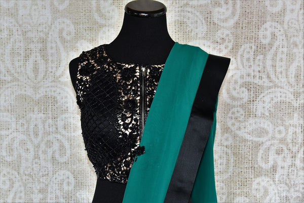 90D248 Georgette saree with black butis & an black embroidered designer blouse. This green saree is perfect for parties and wedding receptions. Buy it online at Pure Elegance.