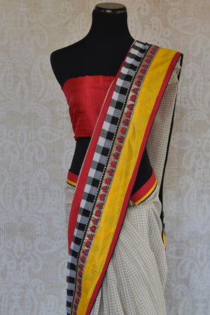90A824 White saree with pops of yellow & red that is versatile & will work as a wedding outfit & as a party saree! Buy this linen saree online at Pure Elegance in USA and you'll love it's addition to your Indian ethnic clothing closet.