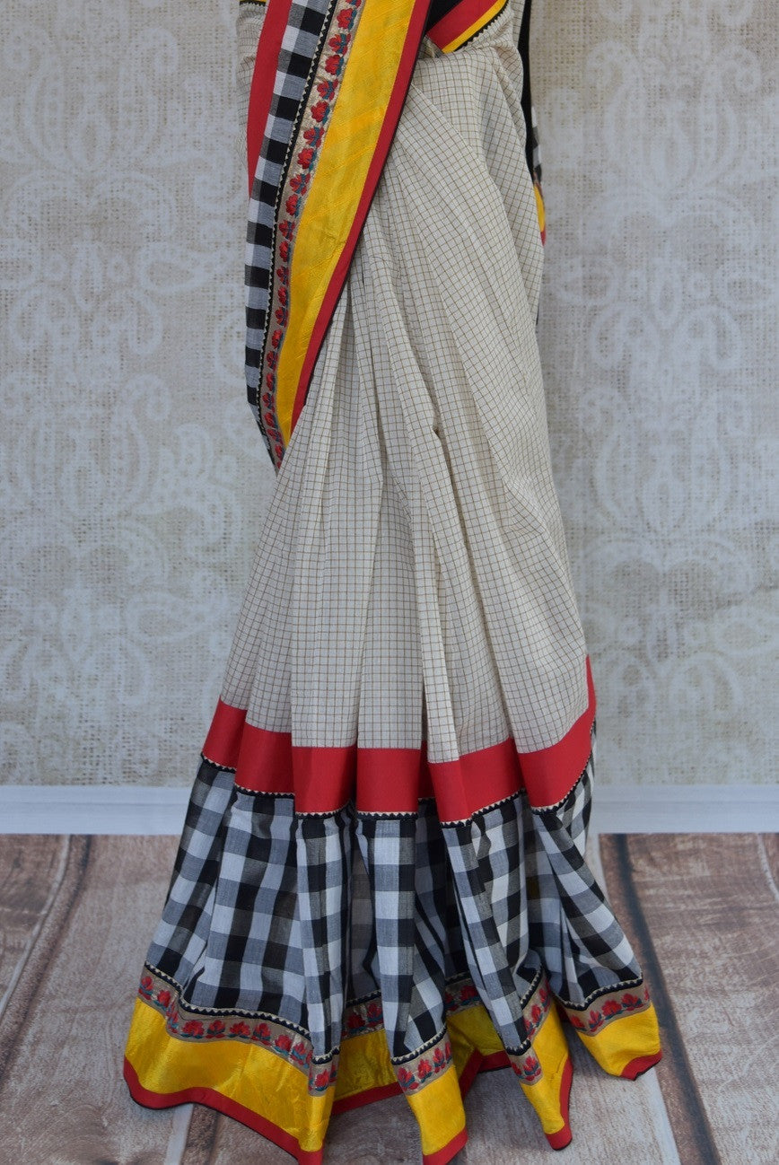 90A824 White saree with pops of yellow & red that is versatile & will work as a wedding outfit & as a party saree! Shop this linen saree online at our store Pure Elegance in USA and you'll love it's addition to your Indian clothing closet.