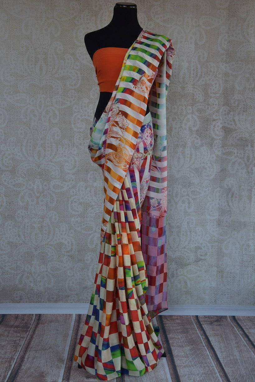 90C176 White and multi-colored checked and striped saree with a floral design. Buy this printed crepe silk saree from India online at our ethnic clothing store in USA. This one is sure to get heads turning.
