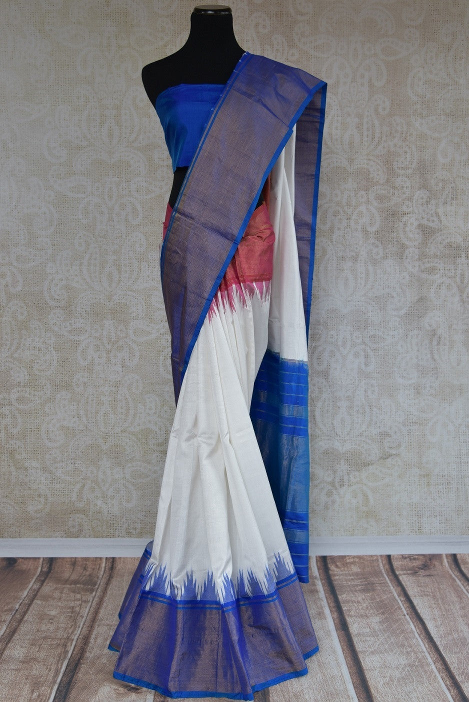 90B767 A silk ikkat saree that makes for a lovely & simple Indian outfit. The blue white & red sari can be bought online at our ethnic Indian wear store online in USA. For parties, as well as ethnic festivities, this saree is a versatile hit!