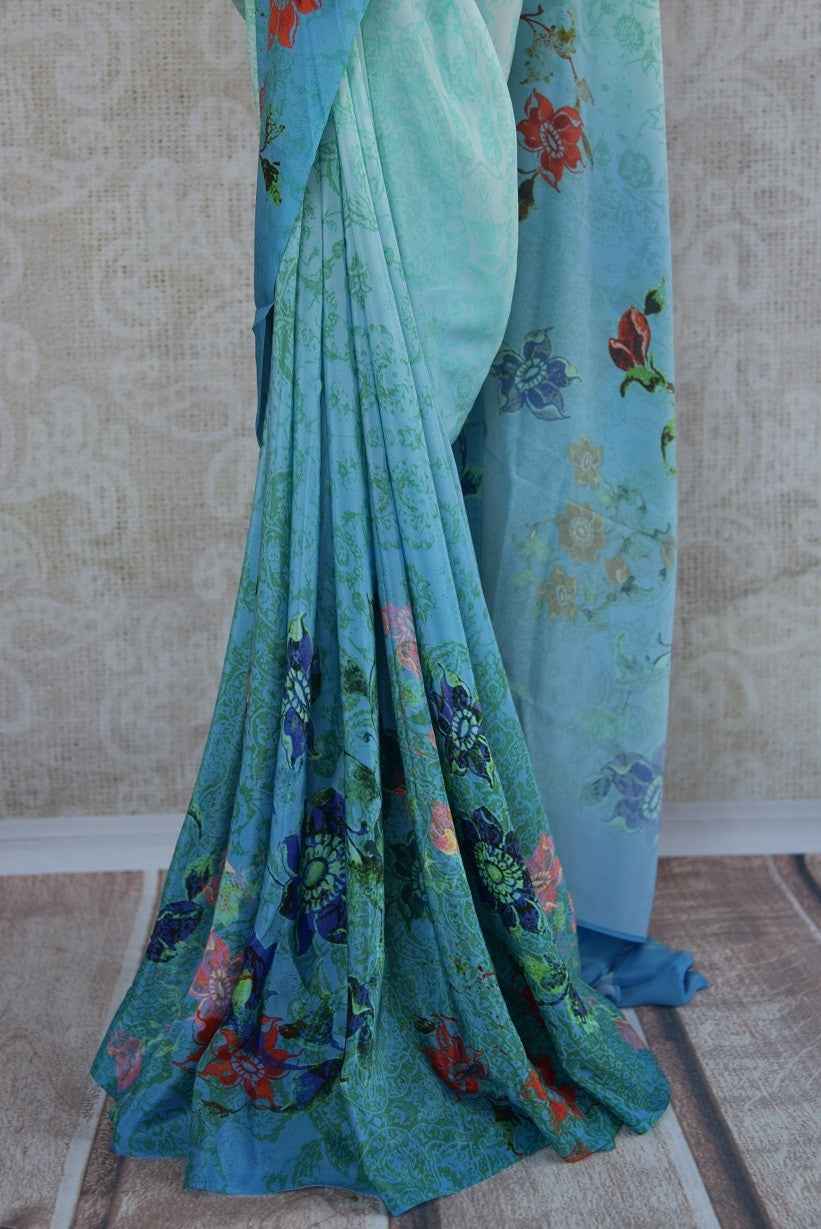 90C165 A refreshingly stylish, shaded blue crepe saree that makes for a lovely pick for pujas and festivities. Buy this traditional floral printed saree online in USA at our ethnic clothing store - Pure Elegance.