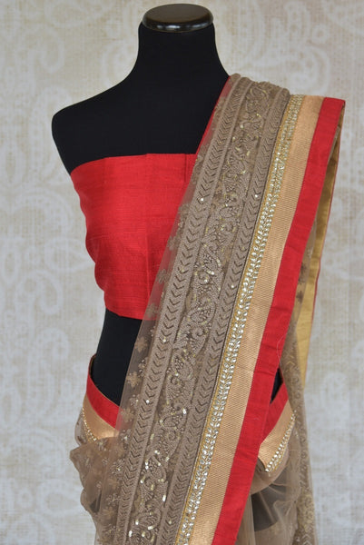 90A804 Brown & red net saree that's perfect for Indian party wear. This embroidered designer saree for sale online at Pure Elegance is topped with a raw silk border and some beautiful kundan work too!