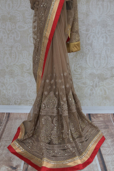 90A804 Brown & red net saree that's a lovely pick for parties and festive occasions. This embroidered designer saree for sale online in USA at Pure Elegance is topped with a raw silk border and eye-catching kundan work too!