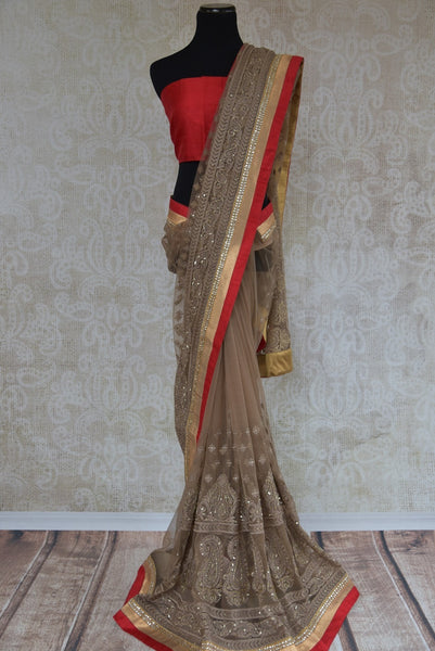 90A804 Brown & red saree that's perfect for Indian party wear. This embroidered designer saree for sale online at Pure Elegance is topped with a raw silk border and some beautiful kundan work too! Buy this net saree from our store today!
