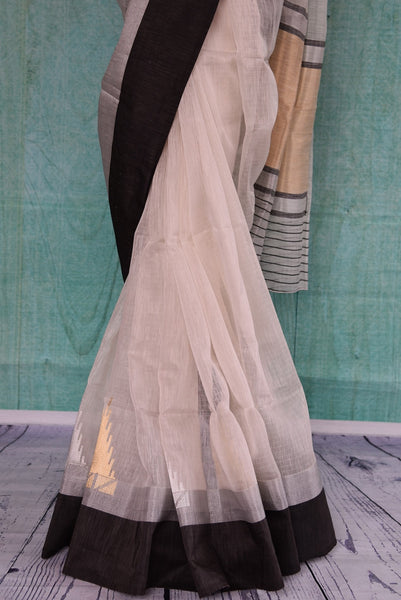 90B988 Buy this beautiful white sari with a black border and gold & silver work at our Indian clothing store online in USA. The traditional chanderi saree makes for ideal ethnic festive wear and party wear that's simple, yet striking.