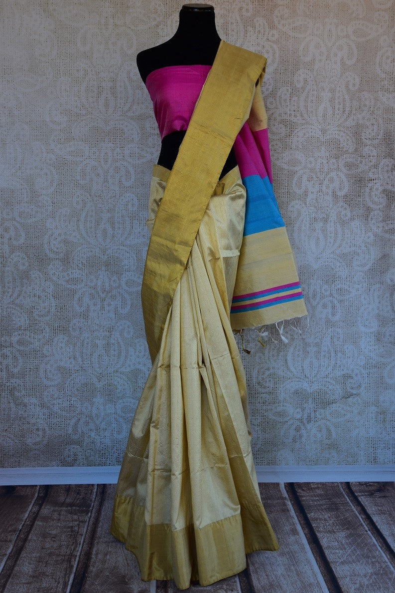 90C293 Simple cream saree with a golden border and color blocked pallu. Buy this raw silk saree, ideal for pujas and festivals, at our Indian clothing store in USA. Buy this simple, yet striking saree from Pure Elegance.