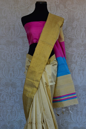90C293 Simple cream saree with a golden border and color blocked pallu. Buy this raw silk saree, ideal for pujas and festivals, at our Indian clothing store in USA. This saree is a sure shot hit, no matter what the season!