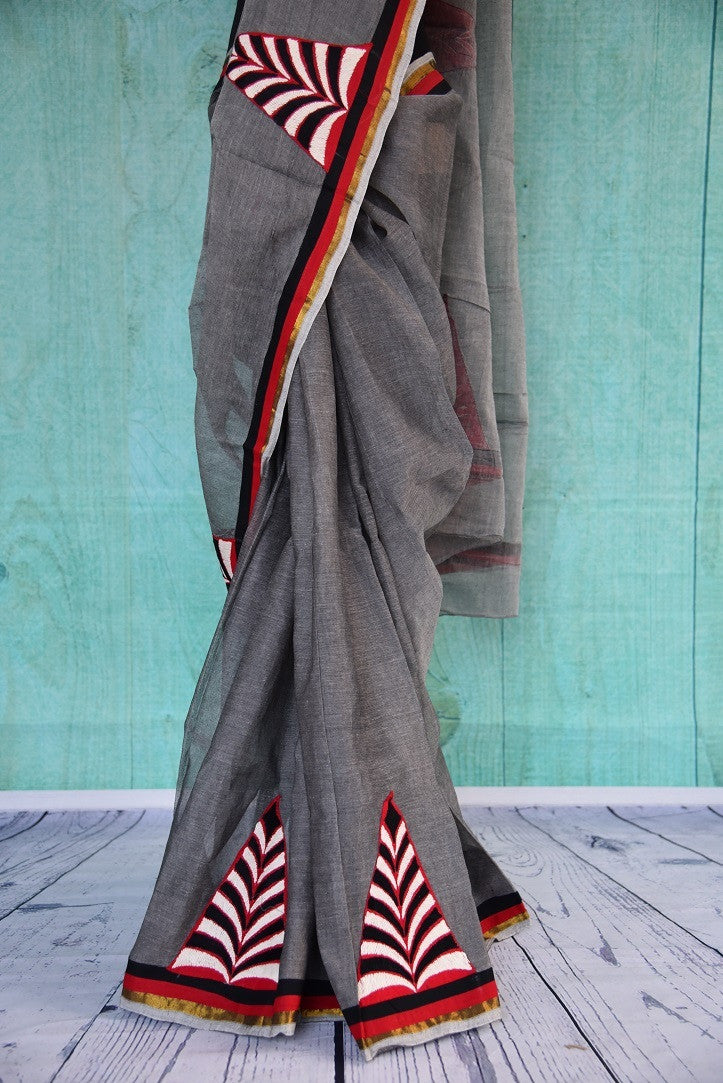 90C077 A unique grey Bengal handloom saree with bold motifs and a border in red, black and white hues. The striking party wear saree is available to buy at our Indian clothing store in USA - Pure Elegance. This unique saree is sure tot urn heads wherever you go.