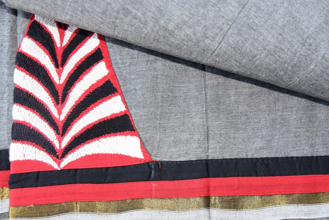 90C077 A unique Bengal handloom saree in grey color with pops of black, red and white. The party wear saree is available to buy at our Indian clothing store in USA - Pure Elegance. This bold saree is sure tot urn heads wherever you go.
