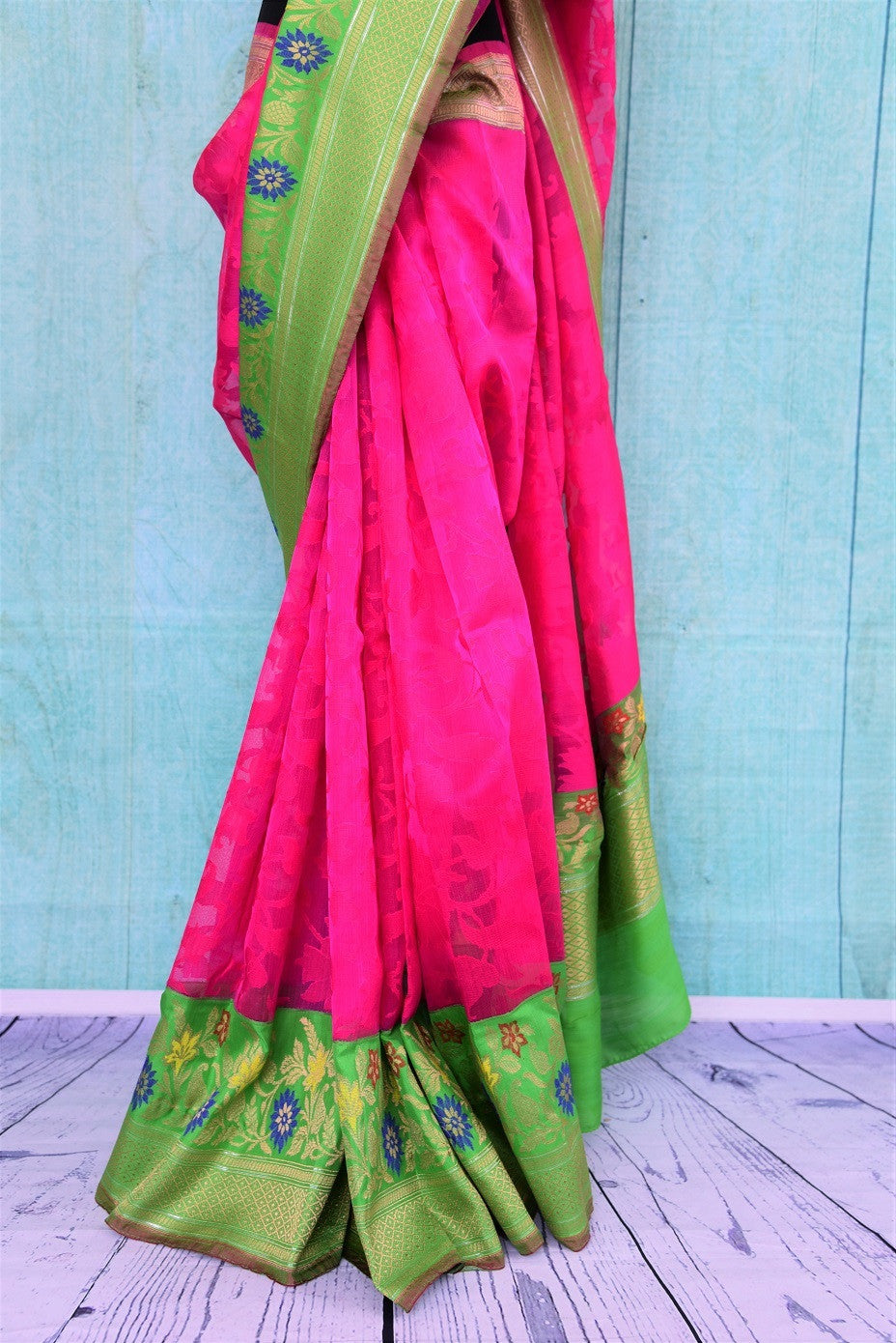 90B969 Vibrant pink matka organza Banarasi saree with a green border with a pop of blue. The festive wear saree is available at our Indian wear store online in USA. This beautiful saree is absolutely not to be missed!