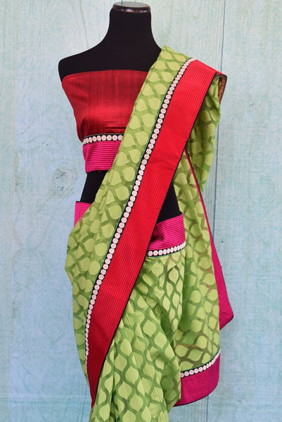 90A821 Green jute saree with a classic Indian pattern and bright red border that makes for a lovely ethnic outfit. The simple traditional saree can be bought at our Indian wear store - Pure Elegance, online in USA.