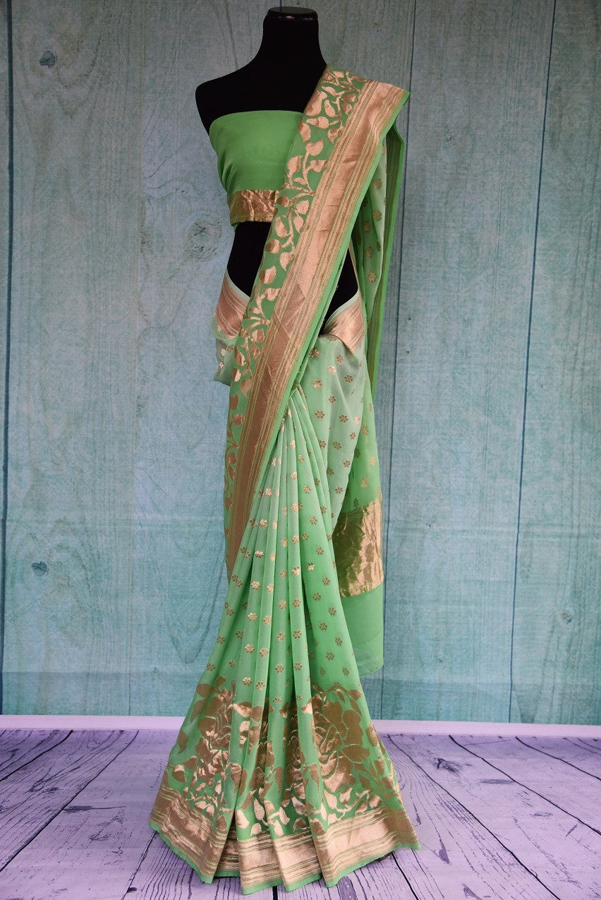 90B984 Pista green and gold Benarasi saree with floral design on the borders. The traditional Indian saree makes for an ideal ethnic outfit for Indian weddings. Buy this saree online at Pure Elegance.