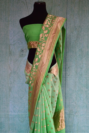 90B984 Traditional Banarasi saree with floral design on the borders. The traditional Indian saree in a refreshing shade of pista green topped with gold, makes for an ideal ethnic outfit for Indian weddings and functions. Buy this saree online at Pure Elegance.