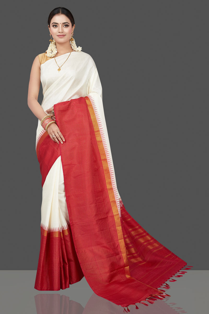Shop beautiful cream Kanjeevaram sari online in USA with red zari border. Look traditional on weddings and special occasions in beautiful Kanjivaram silk saris, pure silk sarees, Banarasi sarees, handwoven sarees, embroidered sarees from Pure Elegance Indian fashion store in USA.-full view