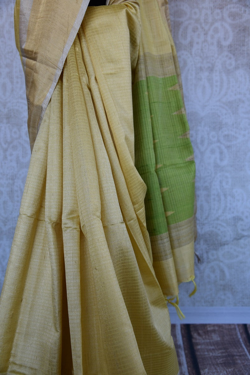 90C292 Lovely yellow saree with a simple green blouse. The simple raw silk saree, ideal for festive occasions and pujas, can be bought at our ethnic wear store in USA. This charming saree is the perfect pick for this season!
