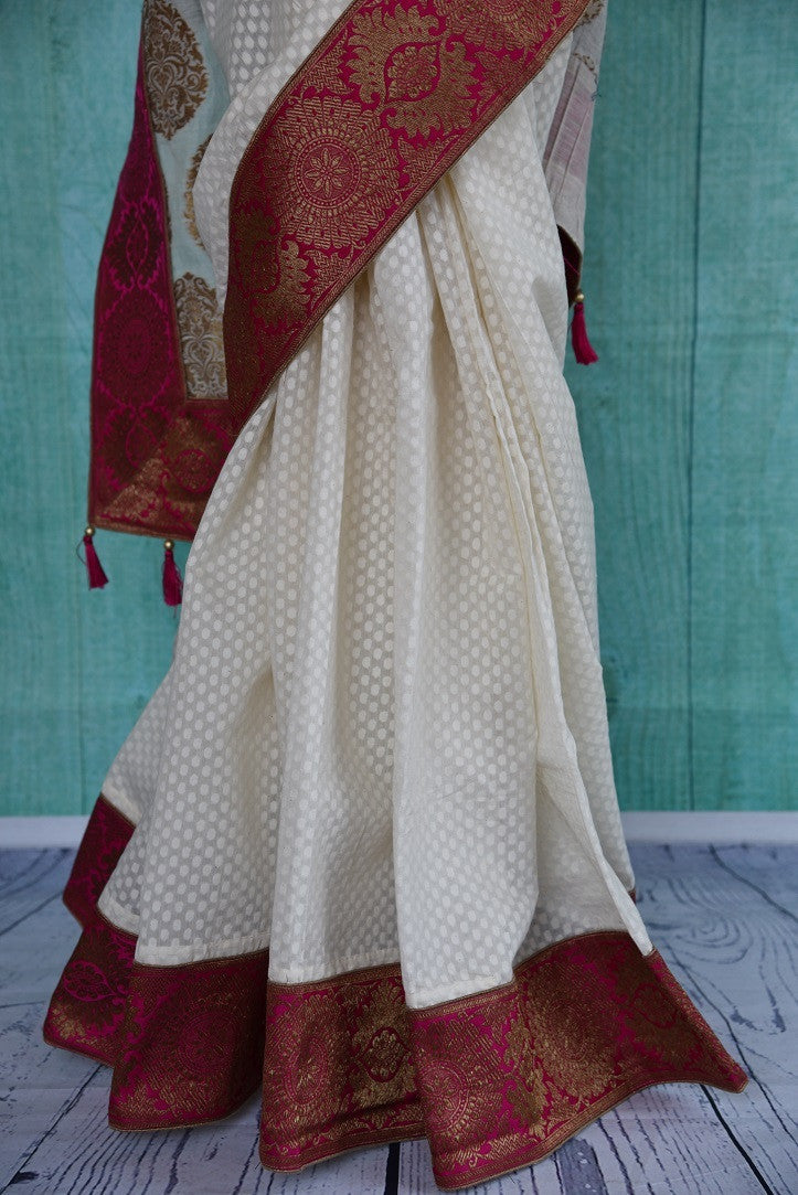 90B038 Classic red and white traditional saree online in USA, topped with golden motifs on the pallu. Buy this linen Banarasi saree at our store Pure Elegance which houses saris, jewelry, lehengas and all things Indian fashion.