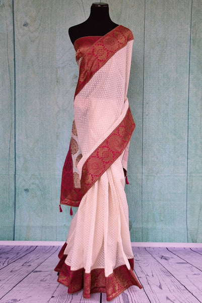 90B038 Classic red and white traditional saree with golden motifs on the pallu. The linen Banarasi saree is available at our store Pure Elegance which houses saris, jewelery, lehengas and all things Indian fashion.