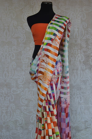 90C176 Bold white and multi-colored checked and striped saree with a floral pattern and an orange blouse. Buy this printed crepe silk saree from India online in USA at our ethnic fashion store.